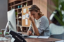 Exhausted businesswoman having a headache at office. Mature creative woman working at office desk feeling tired. Stressed casual business woman feeling eye pain while overworking on desktop computer.