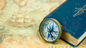 The Compass Beside A Blue Book With A Cross On The Cover. The Compass And The Book Is On Top Of A Na