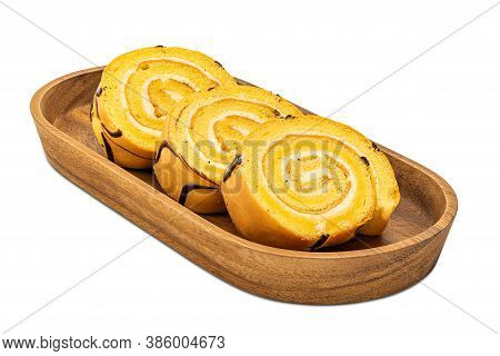 Sliced Cake Roll In A Wooden Tray Isolated On White Background With Clipping Path.