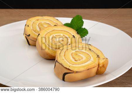 Sliced Homemade Cake Roll In White Ceramic Plate On Wooden Table.