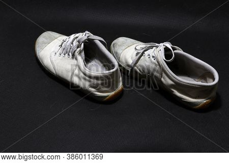 Used Sneakers Shoes In White Color But It Grimy And Gloomy Color, Put Pair On Black Floor. It Is A S