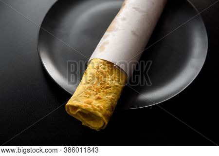 Flour Tortilla With Filling On A Platter. Fast Food Photo Subject On A Black Background.
