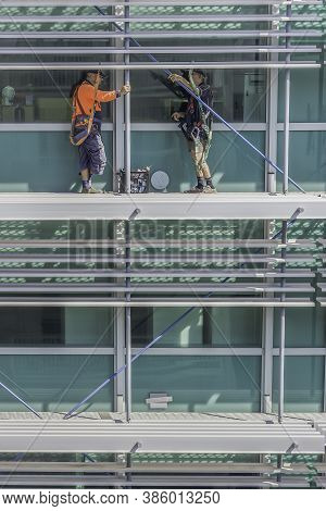 Darwin, Australia - March 14th, 2020: Two Men Working On The Outer Wall Of A Tall Building In Darwin