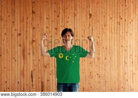 Man Wearing Cocos (keeling) Islands Flag Color Of Shirt And Standing With Raised Both Fist On The Wo
