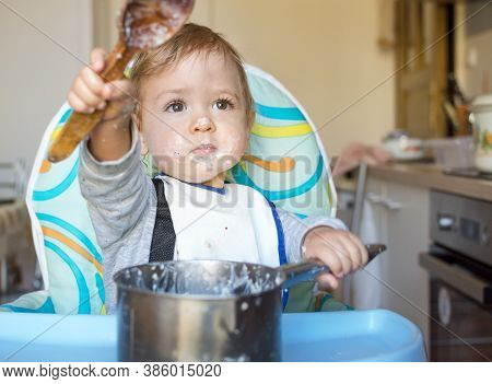 Funny Baby Child Getting Messy Eating Cereals Or Porridge By Itself With A Wooden Spoon, Straight Fr