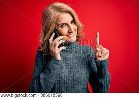 Middle age beautiful blonde woman having conversation talking on the smartphone surprised with an idea or question pointing finger with happy face, number one
