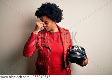 Young African American afro motorcyclist woman with curly hair holding motorcycle helmet tired rubbing nose and eyes feeling fatigue and headache. Stress and frustration concept.