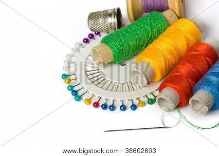Photo of sewing accessories (threads, pins and needle) on a white background