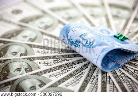 High Dollar, Devaluation Of The Real, 100 Brazilian Reais Banknote Among Many Hundred Dollar Bills,