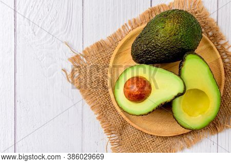 Avocado Half On Wood Plate On White Wood Background And Copy Space. Ripe Fresh Green Avocado