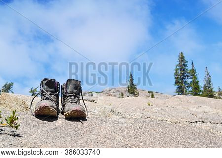 Pair Of Old, Dusty Hiking Boots On A Rock At The Sierra Nevada, To Illustrate The Concept Of Adventu