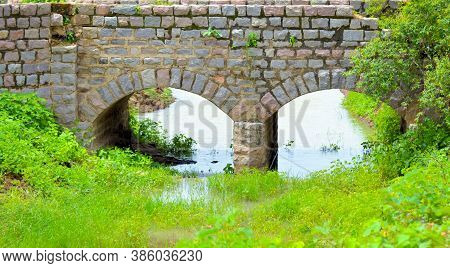 Old Stone Double Arch Bridge. Famous Ancient Stone Arch Double Track Road Bridge In The Forest. View