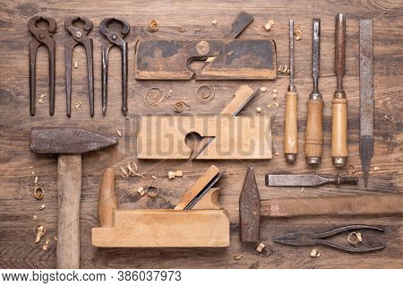 Collection of vintage carpententry tools on old wooden background, top view