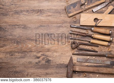 Collection of vintage carpententry tools on old wooden background, top view with copy space