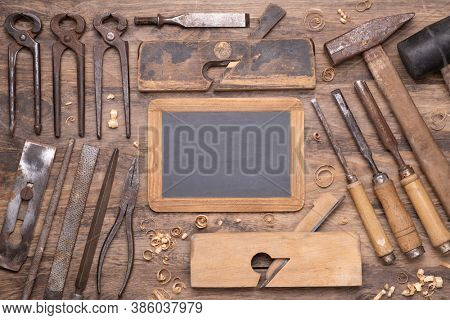 Collection of vintage carpententry tools on old wooden background and empty small chalk board top view with copy space