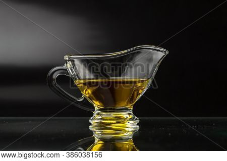 Vegetable Oil On A Black Background. Olive Oil In A Glass Gravy Boat.