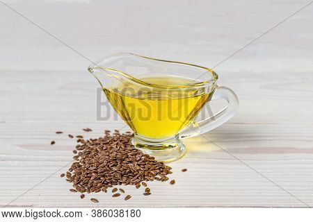 Flaxseed Oil In A Glass Gravy Boat. Flax Seeds On A White Background.