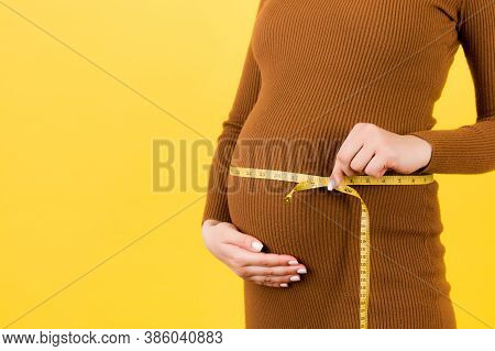 Close Up Of Pregnant Woman In Brown Dress Measuring Her Growing Belly At Yellow Background. Expectin