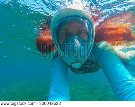 Red Hair Woman In Snorkeling Mask Underwater Photo. Tropical Seashore Snorkeling And Diving Concept.