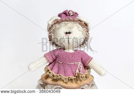 Handmade Knitted Toy Cat. Knitted Cat On A White Background. Portrait Of A Toy. Knitted Clothing For