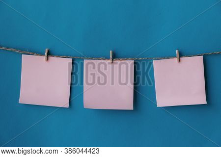 Three Pink Sheets Of Paper With Place For Text Hanging On Rope Isolated Blue Background. To Do List.