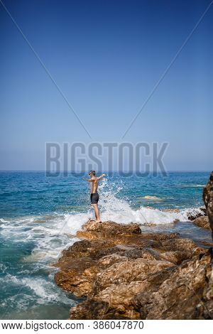 A Young Man Stands On The Rocks Overlooking The Open Mediterranean Sea. A Guy On A Warm Summer Sunny