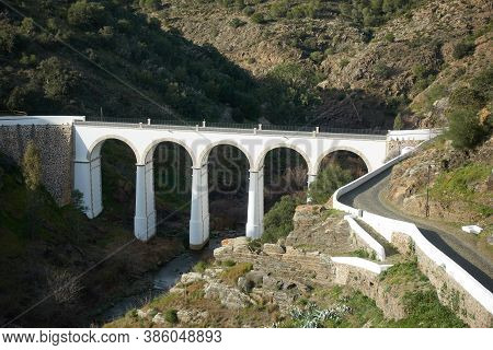 Mertola Beautiful White And Stone Bridge On The City Entrance With Almond Trees On The Landscape In