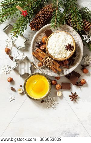 Ingredients For Christmas Baking - Chocolate, Spices, Nuts, Flour And Eggs On A Stone Background. To