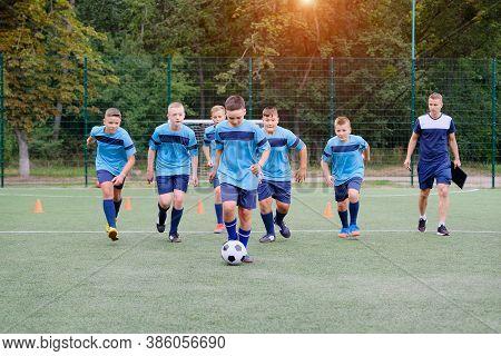 Children Running And Kicking Soccer Ball On Football Training Session