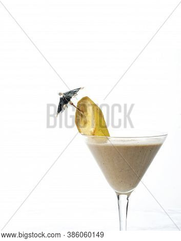 Banana Smoothie In An Elegant Glass Isolated On White With Copy Space.