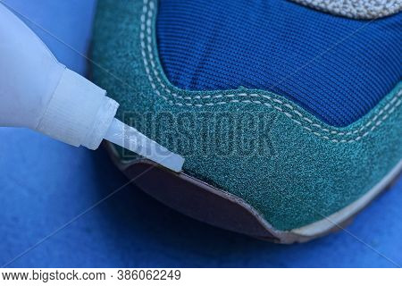 White Tube In Hand Glue The Sock Of A Suede And Leather Sneaker On A Blue Background