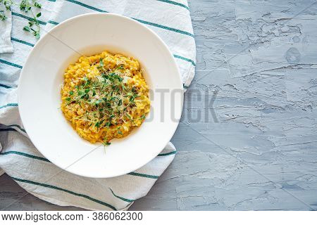 Pumpkin Risotto With Parmesan On Grey Concrete Background, Space For Text, Copy Space. Top View.