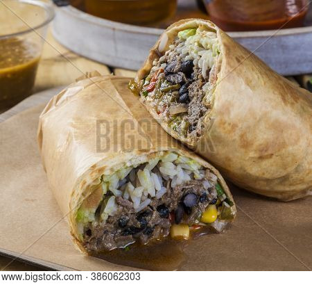 Mexican Take Away Food. Burrito With Rice, Meat, Frijoles And Corn. Take Away Food Wrapped In Paper.