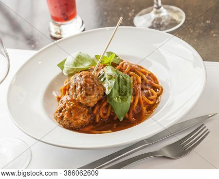 Spaghetti And Meatballs Dish With Tomato Sauce And Basil Leaves.