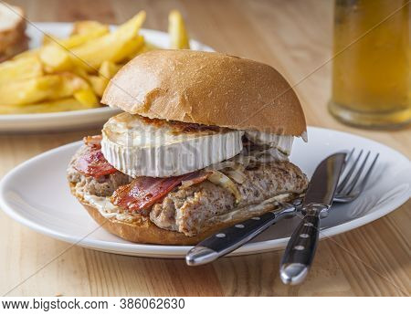 Natural Sausage Burger With Fried Onion, Bacon And Goat Cheese.
