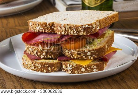 Pastrami Sandwich On Whole Wheat Bread With Mustard, Cheese And Tomato.
