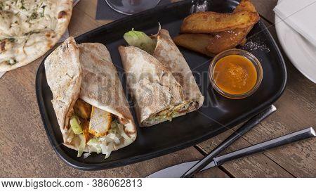 Indian Food. Chicken Tikka Wrap Sandwich On Black Plate.