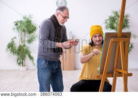 Young man taking lesson from old painter