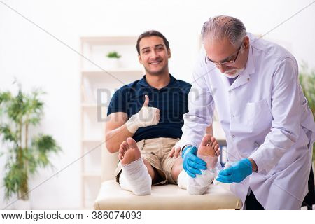 Young injured man visiting old doctor traumatologist