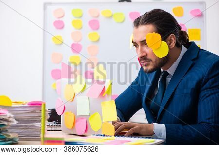 Young male employee in conflicting priorities concept