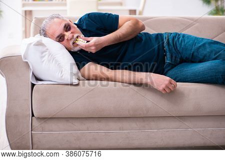 Old man with injured eyes resting at home