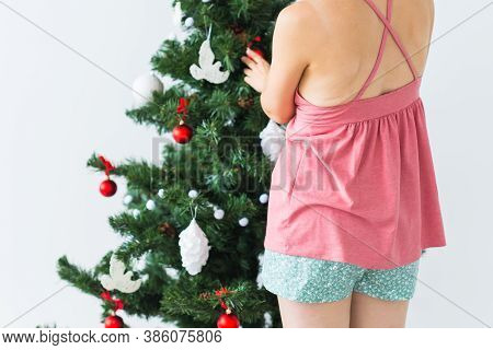 Close-up Back View Of Woman Decorating A Christmas Tree. Holidays And Celebrations Concept.