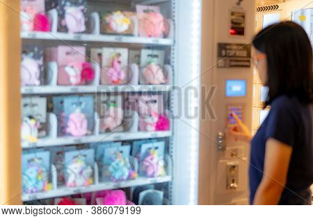 Blur Asian Woman Pressing Button On Vending Machine To Buy Doll. Female Tourists Buying Doll At Auto