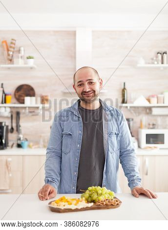 Guy Standing At Kitchen Counter With A Variety Of Tasty And Assorted Cheese On Wooden Plate Looking