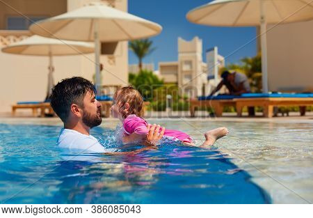 Happy Father With Baby Daughter Are Having Fun In The Pool During Summer Vacation
