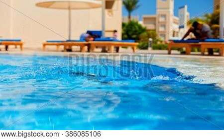 Splash Of Water In The Pool At Sunny Day
