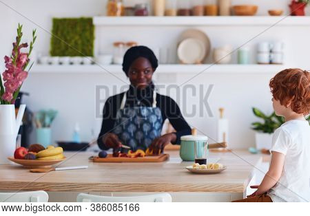 Cheerful Multiracial Family, Mother And Son Preparing The Food On The Kitchen