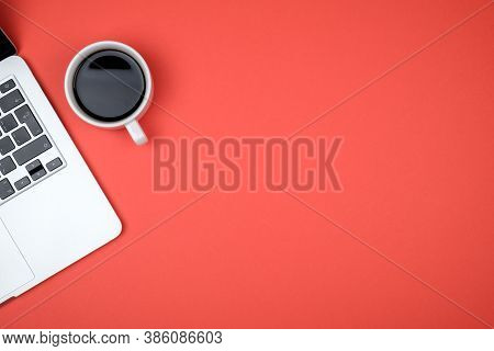 Top View Of Workspace With Laptop, Cup Of Coffee And Copy Space On Colored Background