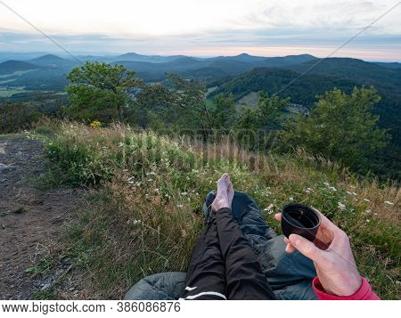 Hiker Wake Up And Drinking Tee. Man Slept In Sleeping Bag On Hill Summit And Before Continue Take Br