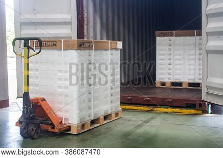 Hand Pallet Truck Loading Shipping Boxes And Goods On Wooden Pallet At Loading Dock From Container.(